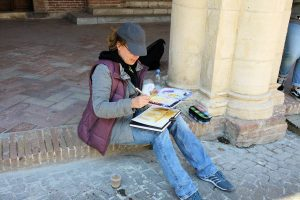 Eine Frau sitzt im Freien und malt mit Aquarell.