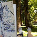 Bäume und das Hessingschlösschen im Hintergrund bei strahlendem Sonnenschein gezeichnet.