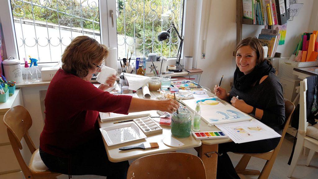 Zwei Frauen malen Tiere in der Aquarelltechnik.